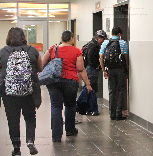 A group of what appears to be able-bodied students walk into an elevator April 8 on the second floor of Moody. A sign next to the elevator states its use is limited to faculty, staff and disabled people. Katherine Garcia
