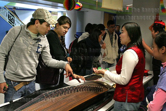 Finance sophomore Celina Chen talks to art freshman Carlos Gloria and nursing freshman Cristina Rivera about a 21-string Chinese instrument called a guzheng during International Education Week Nov. 17, 2009, in the Fiesta Room of Loftin. This year's IEW events begin Monday and end Friday. File