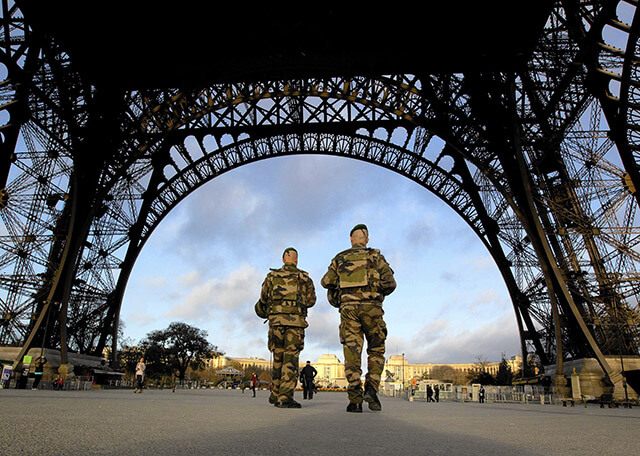 French soldiers patrol the Eiffel Tower, which remained closed the first three days of national mourning following Friday's attacks in Paris.  AccuNet/AP