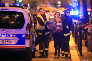 Rescue workers help a woman after the shooting at the Bataclan theater Friday in Paris. Islamic State group claimed responsibilty for the attack and two other simultaneous incidents which killed 129 and injured 352.   AccuNet/AP