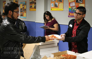 Federico Gonzalez-Vidal, fine arts sophomore and Student Government Association secretary, serves pizza to EMT freshman Chris Rubio Thursday in the Fiesta Room of Loftin. Photo by Kyle R. Cotton