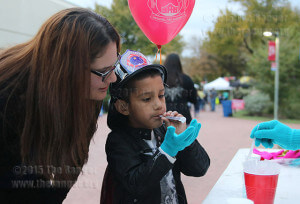Dental assistant sophomore Karen Reyes explains to her son Gabriel, 6, how to blow bubbles at the STEMulate booth at SACtacular Nov. 6 in the mall area. The bubbles, containing dish soap and distilled water, could stick to the blue mittens that were being worn. Photo by Danielle Kelly