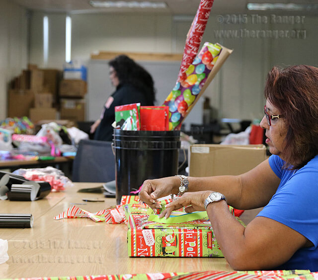 Administrative assistant Sylvia San Miguel secures an ornament to an Angel Tree gift Dec. 3 in Room 643 of Moody. The ornaments contain the name, age and gender of a J.T. Brackenridge Elementary School student. Students, faculty and staff are invited to wrap and decorate gifts from 2:30-5:30 p.m. Dec 4, 3:30-8 p.m. Dec. 10, and 10 a.m.-5:30 p.m. Dec. 11 in Room 643 of Moody. Photo by Katherine Garcia