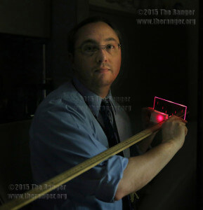 Senior multimedia specialist Aaron Ellis demonstrates the cross-staff he made for astronomy professors today in his office, Room 648 of Moody. A cross-staff is used to take measurements of stars. Photo by Daniel Carde