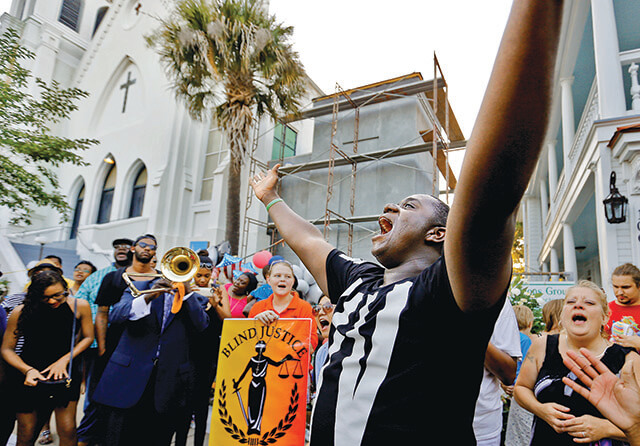 Michael Weeks of North Charleston leads an impromptu praise and worship service in front of Emanuel AME Church June 20, in Charleston. Weeks said he came to pay his respects and felt led to sing and said he was soon joined by others. Paul Zoeller