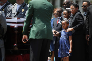 Jennifer Pinckney and daughters, Eliana and Malana, watch as an honor guard carries Sen. Clementa Pinckney, Reverend of Emanuel AME Church, into the Statehouse in Columbia, June 24.  Lauren Prescott