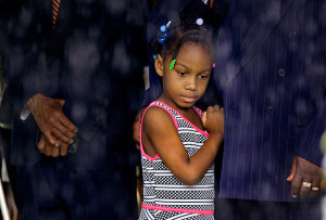 Samariah Johnson, 6, watches from under a tent as rain falls during funeral services for Cynthia Hurd, librarian and community leader, June 27, at Emanuel AME Church.  Paul Zoeller