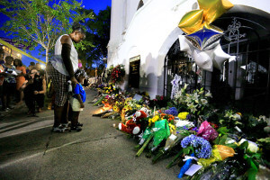 Phyllis Holmes takes a moment to pray with her 3-year-old granddaughter after placing a candle at a memorial on the sidewalk in front of Emanuel A.M.E. Church June 18 in Charleston.  Paul Zoeller