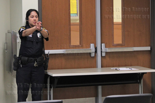 Corporal Marisa Saccio gives a demonstration on blocking doors in case a shooter tries to go in a classroom Tuesday in Room 208 of Nursing.  Monica Correa