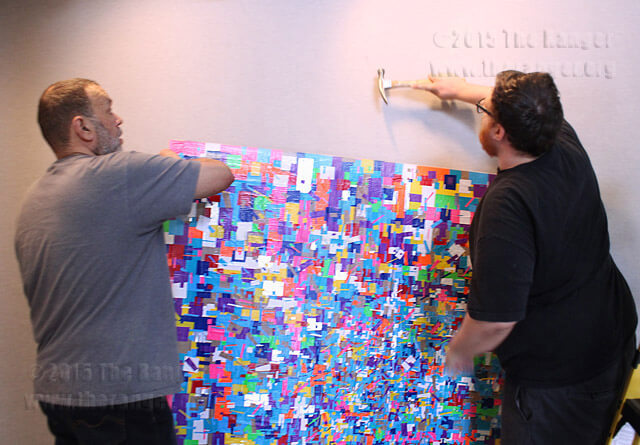 """Painting Professor Ed Rodriguez holds artwork titled """"A Beautiful Uncertainty"""" made entirely of duct tape by his former art student Erick Salazar, while another former art student, James Woodard, hammers a nail in visual arts.  Adriana Ruiz"""