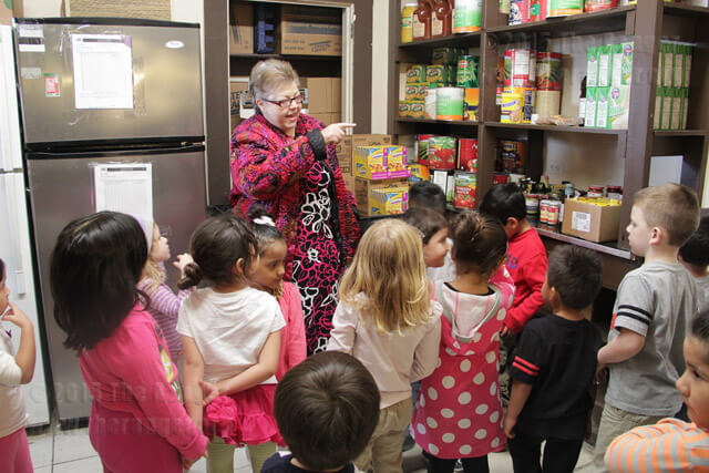 Dr. Alice Johnson, dean of learning resources, shows food storage in the Phi Theta Kappa food pantry to visitors from the early childhood center Feb. 15.  Monica Correa