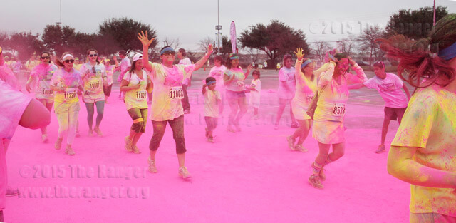 Runners pass through one of four graffiti zones where volunteers throw a nontoxic colored powder Sunday in the parking lot at AT&T Center.   Monica Correa