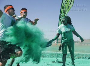 First-time volunteer Rachel Ross covers runners with colored powder as they pass through the green zone.  Daniel Carde