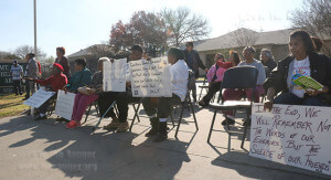 Residents of Mt. Zion Sheltering Arms sit along the sidewalk holding posters with Martin Luther King, Jr.'s inspirational words as they watch the Martin Luther King, Jr. March Monday on Martin Luther King Drive in San Antonio. Photo by Hillary E. Ratcliff