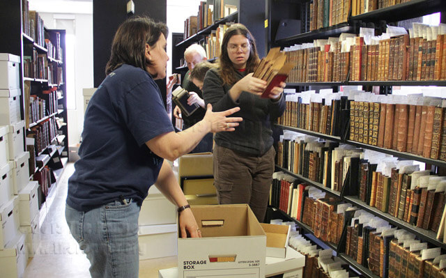 Cait Coker, coordinator of research services at Texas A&M University, College Station, hands books from the Morrison Collection to Robin Hutchison, collection manager lecturer, to pack for transfer to the university Thursday.  Monica Correa