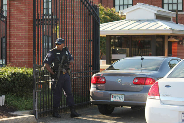 police officer with the U.S. Department of Defense guards the front entrance of the Navy Yard on Tuesday. He allowed some workers to enter the base and turned others away.  SHFWire photo by Zahra Farah