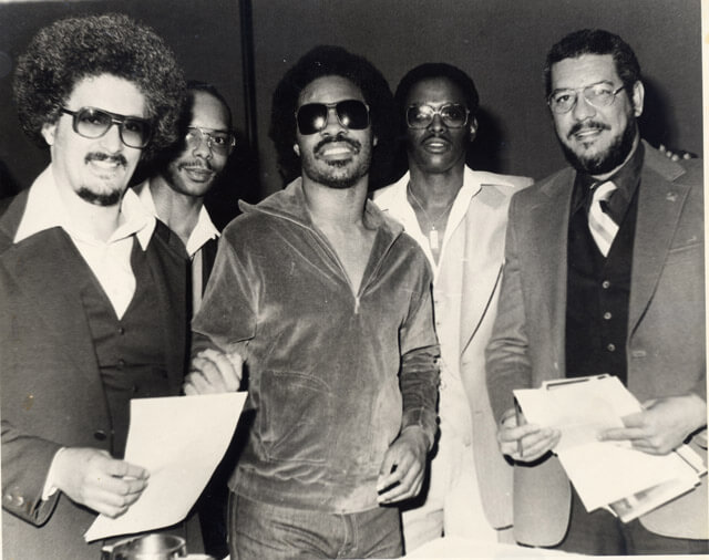 Mario Salas (left), Stevie Wonder (center), John Sanders (fourth from left) meet at the Black Music Board Dec. 7, 1979.  Courtesy