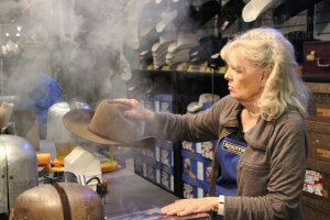 Sugar Reim uses steam to shape a hat at the Circle R Ranch Wear booth.  Carlos Ferrand
