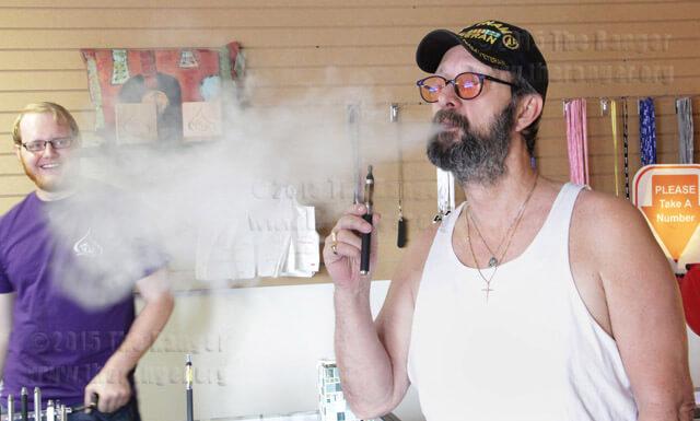 Chris Bolton, Thanks for Vaping clerk, gives 49-year smoker Gary Porton a sample of an e-cigarette Sept. 27. Porton said an e-cig may help him quit.  Ana Cano
