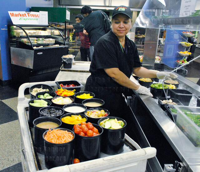 Food service supervisor Maria Rodriguez prepares the salad bar for the lunch crowd Wednesday in the cafeteria at Loftin. The salad bar provides a fresh alternative for students and employees interested in eating healthy. Salads start at $3.99 for a small and $5.99 for a large.  Kirsten Simpson