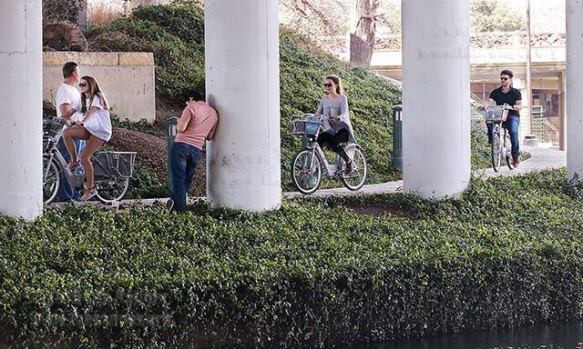 Three cyclists ride along the San Antonio River Feb. 15 under the I-35 bridge on bicycles from the Pearl Brewery station. They and other locals were enjoying the afternoon's unusual 78-degree weather.  Photo by Hillary E. Ratcliff