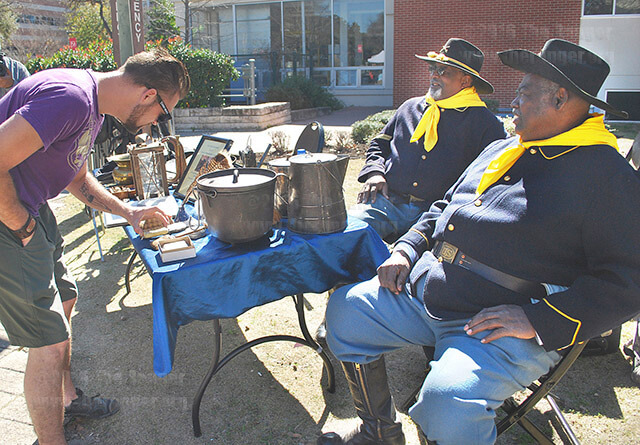 Wildlife biology freshman Curtis Bitterly studies a soap bar on display at the Bexar County Buffalo Soldiers Association encampment Wednesday in the mall in celebration of Black History Month. Clarence Thompson, coordinator, and Clay Leslie, assistant supply, discussed the equipment and supplies available to Buffalo Soldiers of the 19th century. Photo by Aly Miranda