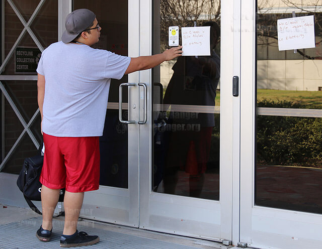 Liberal arts freshman Matt Cuevas reads a notification taped to the north entrance of Candler Tuesday. All classes in Candler were cancelled because of an electrical outage throughout the building. Cuevas said he didn't receive an email about the cancellation.  Photo by Melissa Luna