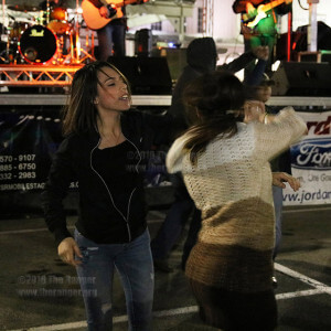 """Jasmine Sanchez, 54th Street Bar and Grill server, spins Patrice Salas, dance partner and Texas Western Warehouse sales associate, as the Clay Hollis Band performs George Strait's """"Write This down.""""  Photo By Kyle R. Cotton"""