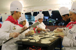 Culinary arts freshman Sandy Dreitzler gets ready to flip flour tortillas as her classmates lay more on the grill to be heated in preparation of the coming crowd.  Photo by Kyle R. Cotton