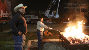 Cowboy Breakfast volunteer Emet Rios waits for firewood to heat up as volunteer Pasqual Valdez Jr. pours lighter fluid onto the fire. Rios uses a wheelbarrow to wheel and shovel red hot wood embers into firepits used to heat and cook the tacos.  Photo By Kyle R. Cotton