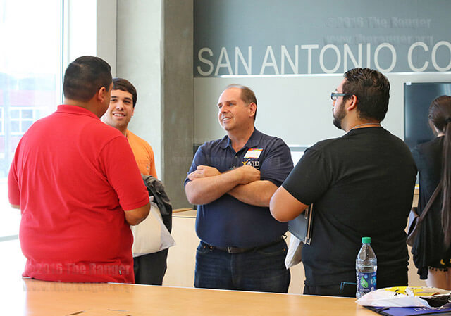 Specialist Nick Silva speaks with Matt and Robert Michaels and Roger Cruz about opportunities here during a tour of the welcome center Feb. 12.  Photo by Ryann Palacios