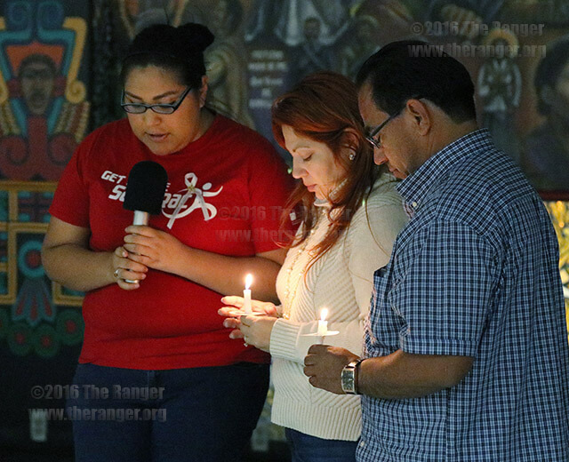 Danielle Sanchez, forensic science graduate and friend of Trevor Anthony Macias, leads a prayer for Macias' parents Elizabeth and Anthony Macias at a candlelight vigil Tuesday in the Fiesta Room of Loftin. Architecture sophomore Trevor Anthony Macias died on Feb. 14 after being hit by an alleged drunk driver. Photo by Alison Graef