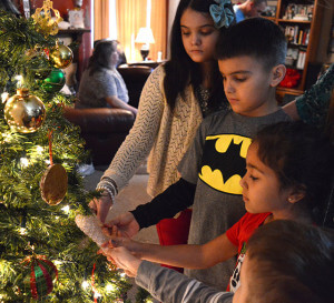 Olivia Cotton, 11, Charles Cotton, 8, Khloe Del Carmen, 5, and Christopher Cotton, 4, put an angel wing ornament on the Christmas tree Dec. 25 at the Cotton residence. The ornament honors their great-grandfather Charles Holden, who died in March, and keeps him with his family in spirit for the holiday season.  Courtesy