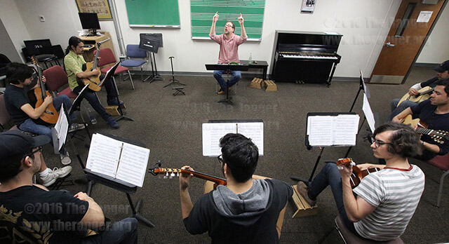 Tom Sprayberry, music adjunct and guitar ensemble director, keeps rhythm for his students Feb. 29 during Guitar Ensemble in Room 102 of the music hall annex. The ensemble performs 7:30 p.m. May 4 in McAllister auditorium. E.  Photo by David Guel