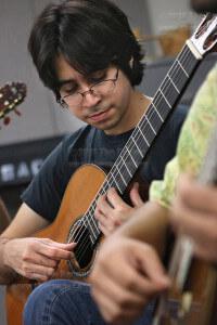 "Music sophomore Giovanni Medrano plucks along to Agustin Barrios Mangore's ""Cueca.""  Photo by E. David Guel"