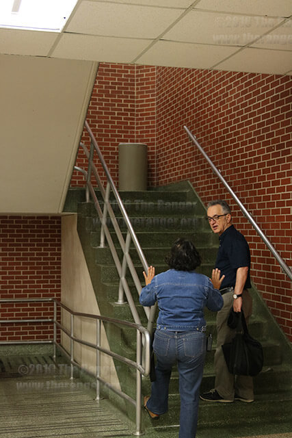 A custodian talks with math Chair Said Fariabi at 7 a.m. Thursday about a leak in the roof of McCreless. Rain water from Thursday's early morning downpour poured into McCreless, down the stairwell and across the lobby to the south exit.  Photo by Wally Perez