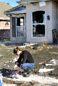 Melissa Babin collects memories from damaged photographs in St. Bernard Parish, December 2005.  File