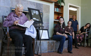 """John Igo reads over """"Easy Reference Guide for Symptoms"""" at the unveiling of the John Igo Health and Wellness Resource Center. Igo gave the book to Katie Dale (center right), resident programs director at Brookdale Hamilton Wolfe Senior Living, as a symbol of his donation of more than 250 medical books Sept. 23, 2015, in the Sun Room at Brookdale at 5331 Hamilton Wolfe Road. File"""