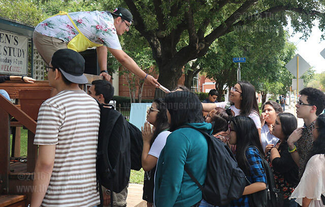 Criminal justice sophomore Stephan Lopez hands an El Paraiso paleta to Celeste Jones, junior at Travis Early College High School, as a part of Weeks of Welcome Tuesday at the Church of Christ Student Center. To celebrate the first week of fall classes, volunteers at the center were giving away free paletas to passersby, and inside the center were free sausage wraps, green beans, salad and drinks. Photo by Alison Graef
