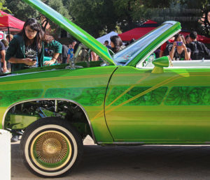 "Drama freshman Emily Sanchez surveys the engine of a 1982 Oldsmobile Cutlass Supreme called ""Southside Hold'n"" during Antojitos Festival Sept. 24, 2014 in the mall. Sanchez said she was interested because her grandfather works on cars and she is learning about them.  File"
