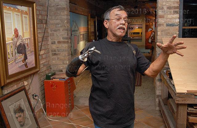 Local artist Jesse Treviño discusses some of his artwork at his studio.  Photo by Derik Villanueva