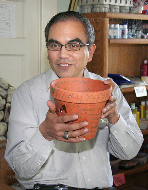 Mortuary science Instructor José Moreno, also an intern at the Children's Bereavement Center of South Texas, shows a flower pot used to help children overcome their grief at the center.  Photo by Altug Sami Icilensu