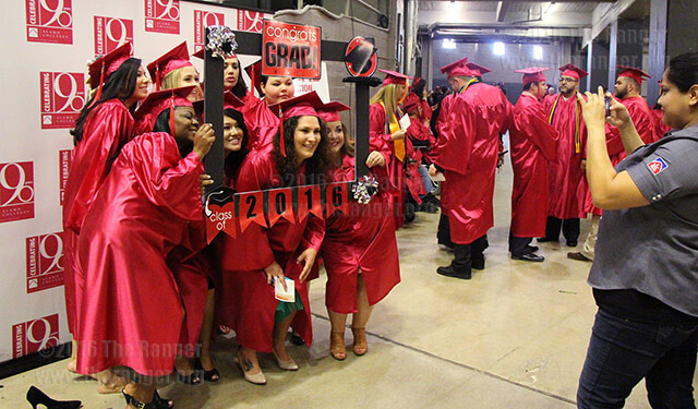 Pam Frias, public relations administrative assistant, takes a picture of a group of graduates backstage before the 2016 commencement. File