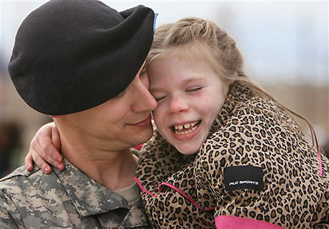 "Capt. Jeff Strauss of the U.S. Army's 4th Infantry Division cuddles with his 7-year-old daughter Jona Strauss at the ""Heroes' Tribute"" at Fort Hood on Feb. 2. Strauss returned Nov. 15, 2006, after a year of duty in Iraq.  Courtesy"