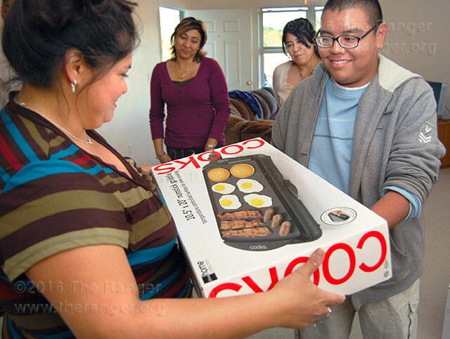 Former Northwest Vista College student Roxanne Faz accepts a housewarming gift from fine arts sophomore James Dominguez Oct. 24.  Photo by Derik Villanueva