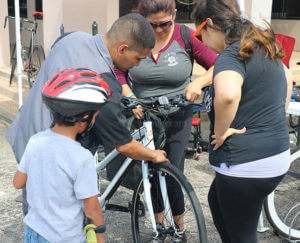 Sonia Trevino, client service specialist for San Antonio Housing Authority, and April Rodriguez, licensed vocational nurse for Brookdale Home Health, watch and listen as Trevino's brakes are tigtened at Síclovia Sept. 25 at Broadway and 10th. Mark Trejo, manager and mechanic of Charles A James Bicycle Shop, tightened Trevino's brakes at the bike shop stand, which he managed. Photo by Zachary-Taylor Wright