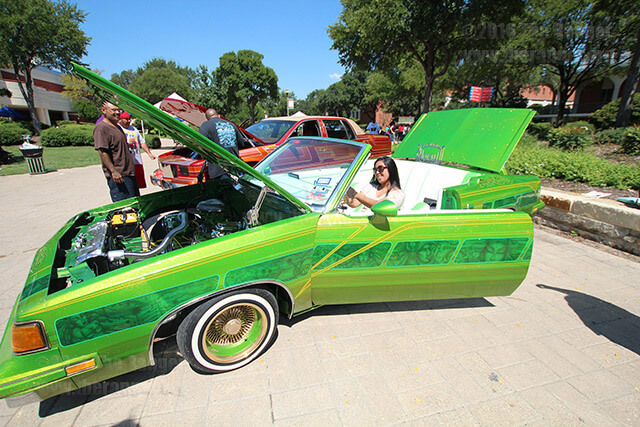Civil Engineering freshman Vangie Santos  sits in a lowrider while a friend snaps a picture on her cellphone during Antojitos for the Hispanic Heritage Month Sept. 25, 2013 in the mall.