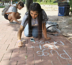 "Political science freshman Iris Castro writes ""Pugs not Drugs"" during Chalk Day Oct. 3 between Loftin and chemistry and geology. Photo by Deandra Gonzalez"