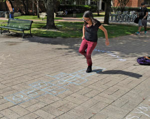 Psychology freshman Marina Morales stops and participates in a quick run of hopscotch during Chalk Day Oct. 3 between Loftin and chemistry and geology. The journalism program and The Ranger sponsored the event to promote freedom of speech. Any students who wanted to express themselves were welcome to participate. Photo by Deandra Gonzalez