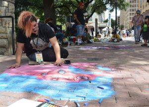 "Fine arts sophomore Anaia Alejandro draws her piece ""Fusion,"" created for the bright appealing colors which were kid friendly during  ""Chalk It Up"" Saturday. Art Guild students were invited to participate in the block-wide mural to draw as emerging artists.  Photo by Deandra Gonzalez"